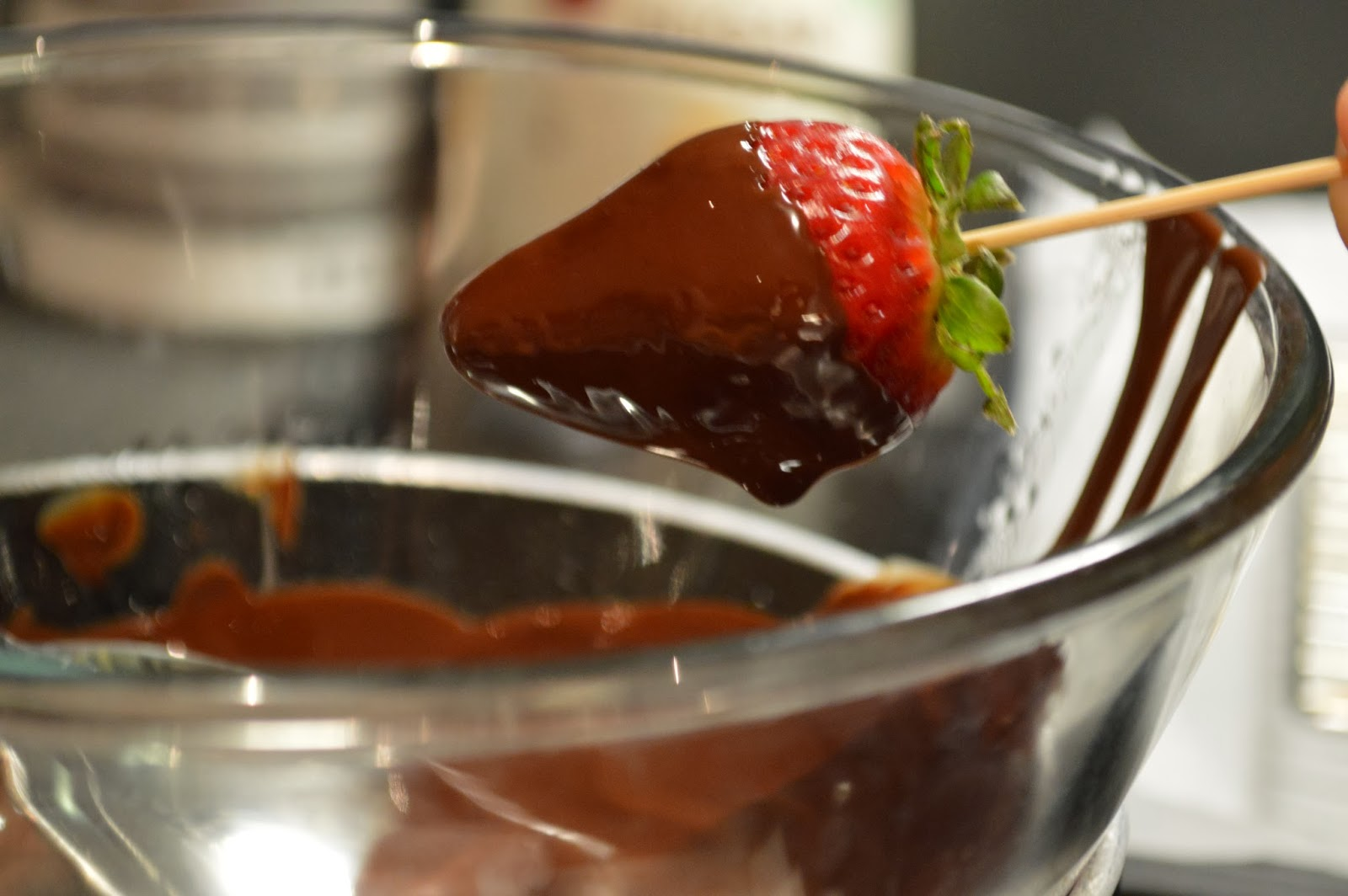 Dip strawberry in melted chocolate sauce