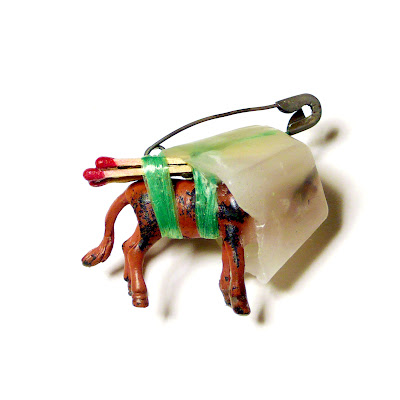 A small brooch which suggests its own purpose might be for burning. It consists of a plastic animal whose head has been set in a block of wax and tied to its back is a number of matches.