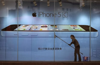 A worker cleans glass in front of an iPhone 5C advertisement at an apple store in Kunming, Yunnan province, in this October 27, 2013 file picture. CREDIT: REUTERS/WONG CAMPION