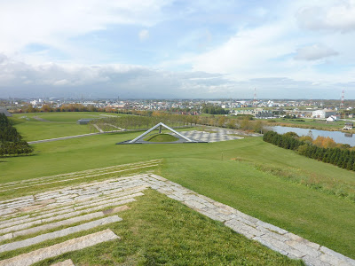 Two sides of play mountain as seen from the top of play mountain with the tetra mound in the background at Moerenuma Park (Moerenuma Koen), Sapporo