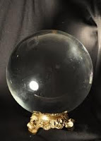 a clear crystal ball on an ornate golden stand