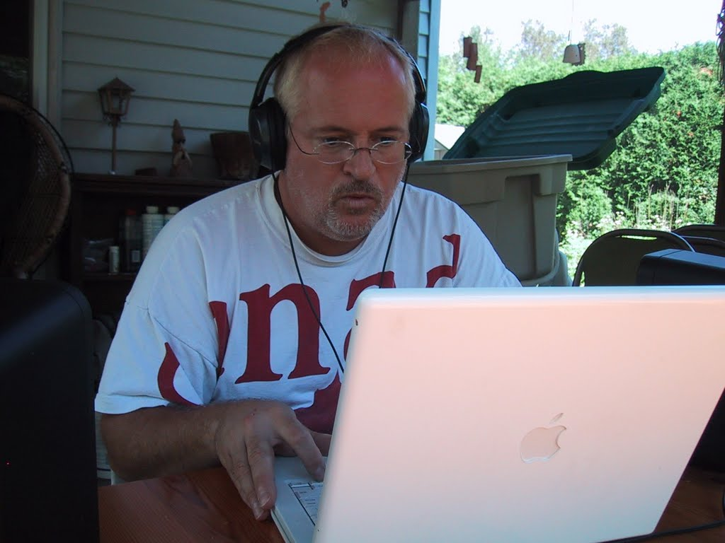 Pierre Massie, Composer of choral music works at his laptop in the sunroom