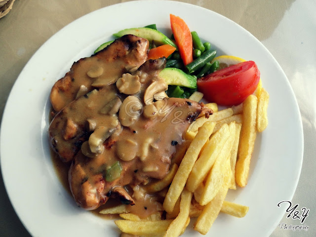 Grilled chicken with mushroom sauce, and sautéed vegetables, and french fries