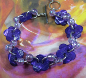 Bracelet has bright purple flower buttons with small light purple accent beads in twist design