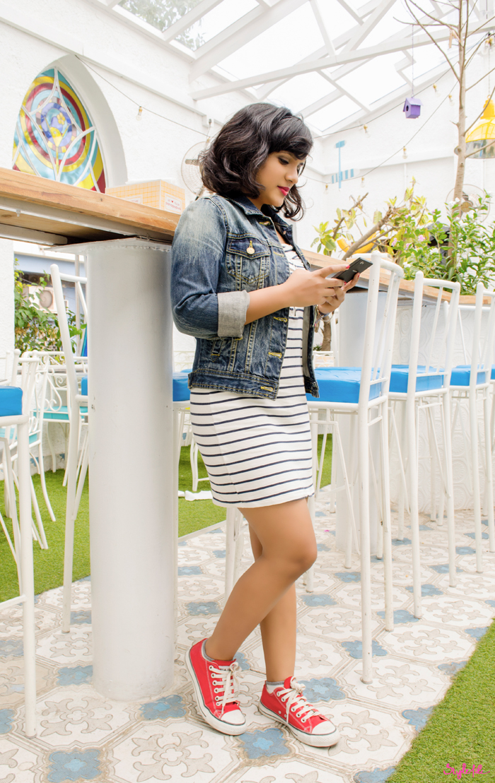 Dayle Pereira of the blog Style File views her Phicomm Passion 660 cellphone while wearing a striped tube dress, denim jacket and red converse sneakers