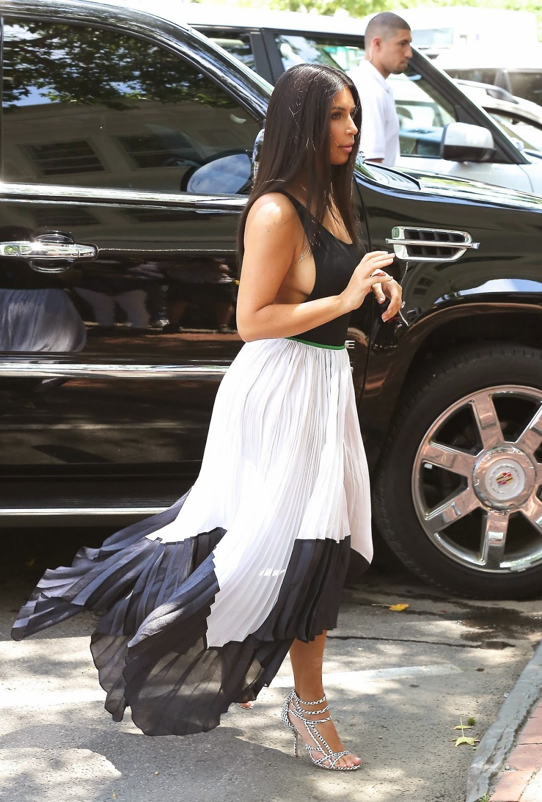 Kim Kardashian steps out in clingy vest and pleated skirt in South Hampton