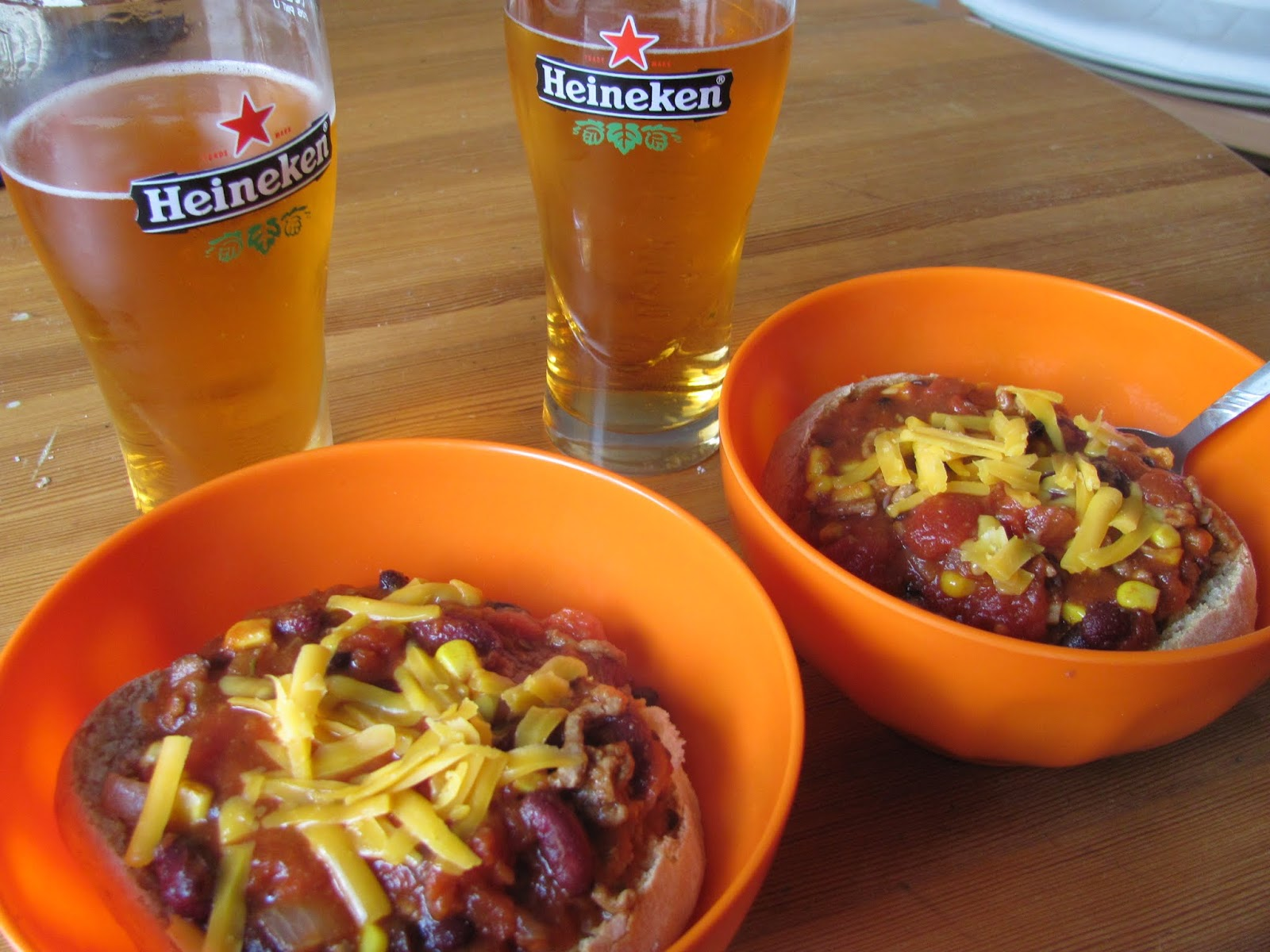 Two bowls of chilli topped with cheese and two glasses of Bulmer's served in Heineken glasses in Dublin, Ireland