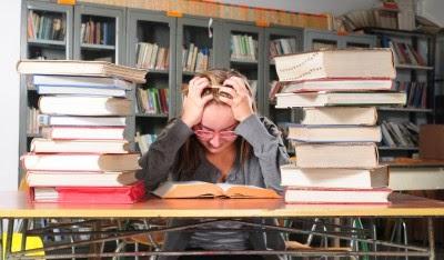 chica estudiando con montones de libros y dolor de cabeza