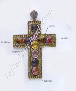 GEM-SET: This silver cross is set with six sapphires and four other gemstones: an inky-blue spinet, an amethyst, a citrine, and a brown zircon. Another sapphire is attached at the top.