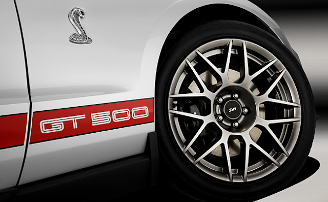 Front wheel of white 2011 Ford Shelby GT 500 showing SVT logo on wheel, &quot;GT500&quot; on stripe and chrome Cobra badge