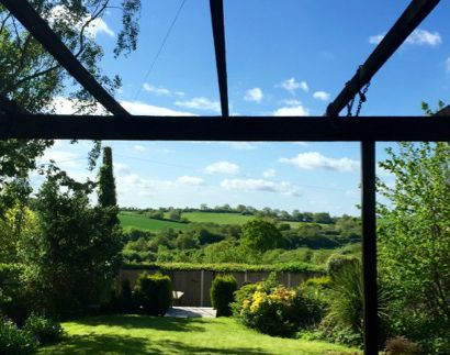 What I Love About Being Home | Morgan's Milieu: A view of a sunny garden and green fields in the distance