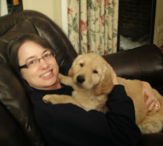 Woman holding golden retriever puppy in her arms while seated in a recliner.
