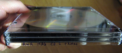 [Image: CD jewel cases with text labels hand-written on the backs but mostly invisible because of the lack of contrast between the black ink and the black plastic showing through the transparent case.]