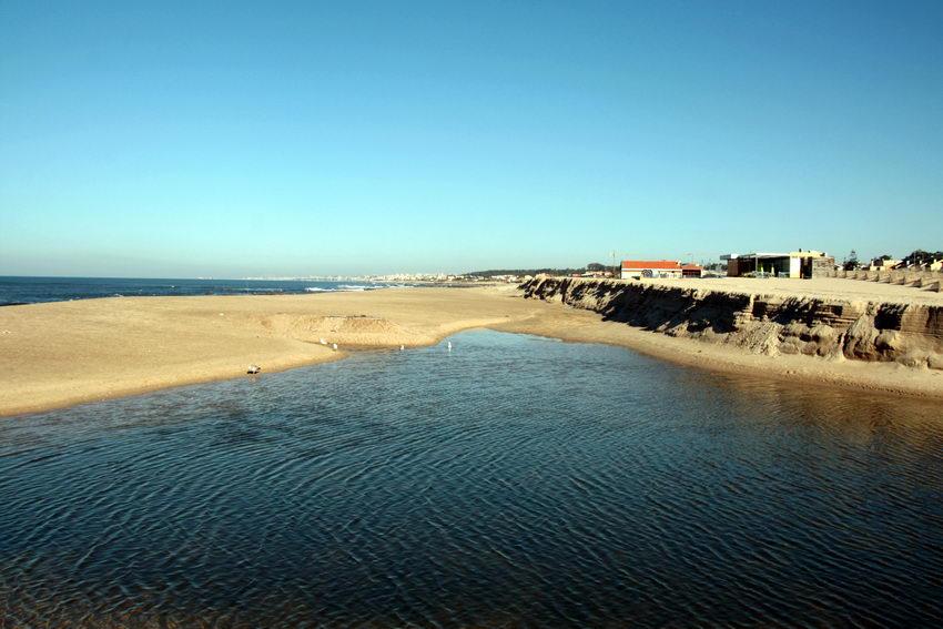 Em primeiro plano, um lago anterior à praia, resultante das águas dum pequeno riacho. A seguir a areia e por fim o mar. Céu limpo.