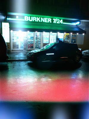 Späti 7/24 im Gegenlicht mit nasser Straße und Lichtstreifen