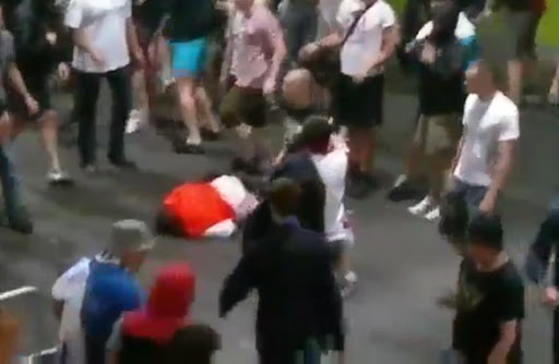 A stadium steward lies on the ground after being brutally attacked by Russian supporters
