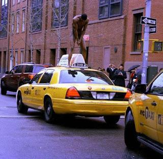 Homem pelado em cima de um táxi