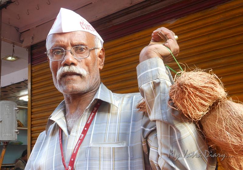 A man selling coconuts at Lalbaugcha raja, Ganesh Pandal Hopping, Mumbai