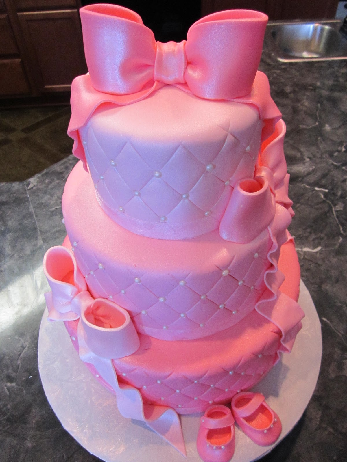 three tier quilted pink pearl baby shower cake with booties bows