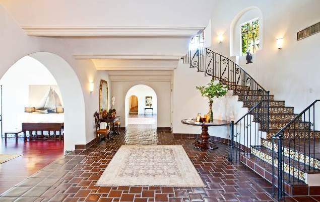 foyer with glazed Saltillo tile floor and stairs with arched entryways into other rooms