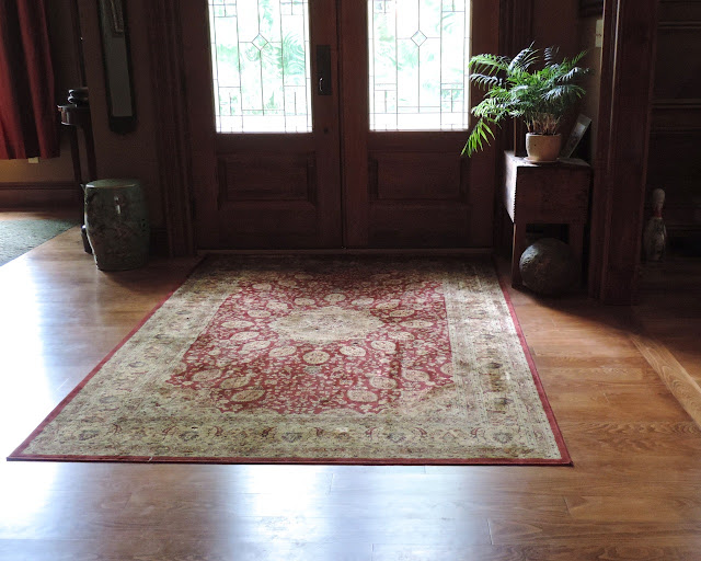 french door entry way with hardwood floors, area rug