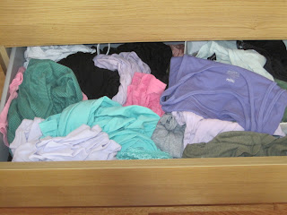 Messy drawer of t-shirts and tanks