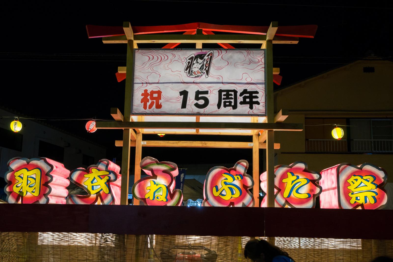 祝 十五周年 羽衣ねぶた祭 と文字が飾られた山車の写真