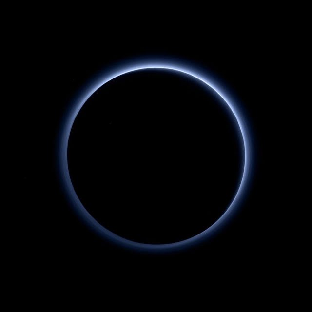 Pluto's Blue Sky: Pluto's haze layer shows its blue color in this picture taken by the New Horizons Ralph/Multispectral Visible Imaging Camera (MVIC). The high-altitude haze is thought to be similar in nature to that seen at Saturn's moon Titan. The source of both hazes likely involves sunlight-initiated chemical reactions of nitrogen and methane, leading to relatively small, soot-like particles (called tholins) that grow as they settle toward the surface. This image was generated by software that combines information from blue, red and near-infrared images to replicate the color a human eye would perceive as closely as possible. (Credit: NASA/JHUAPL/SwRI)