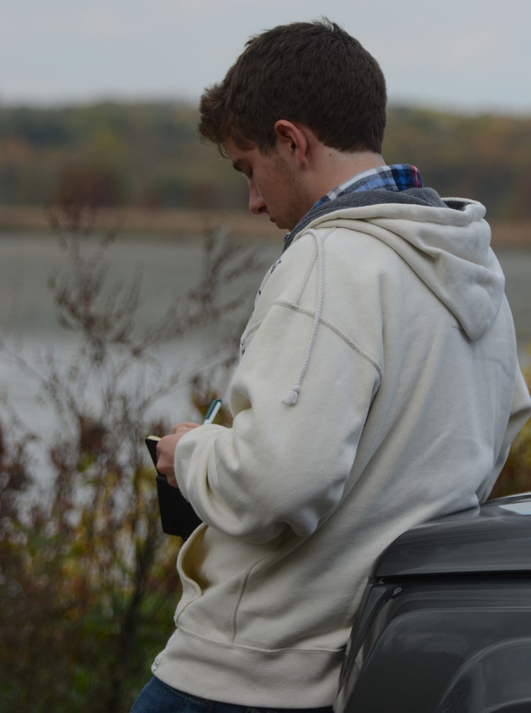 Matthew Riccetti writing in his field journal at Spring Valley Nature Preserve in Waynesville, Ohio.