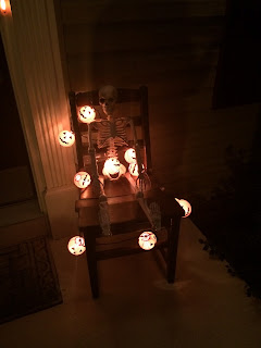 Skeleton seated in our chair for Halloween decor (lights on at night)