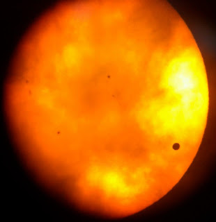 Picture of Venus, the sun, and clouds through a telescope