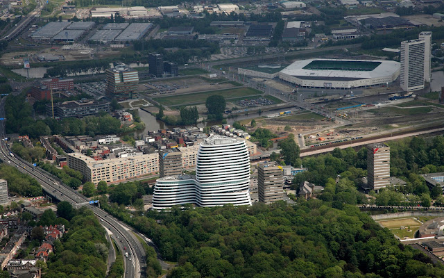 Picture of an office building as seen from the air with the rest of the city in the bacground