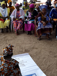 A woman participant works with her group to generate ideas for handling violence at the community level