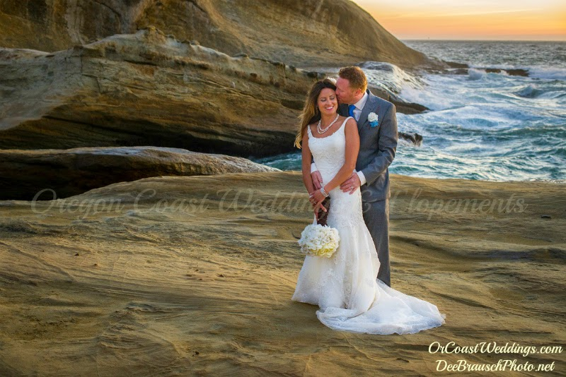 bride and groom standing on Cape Kiwanda with blue ocean