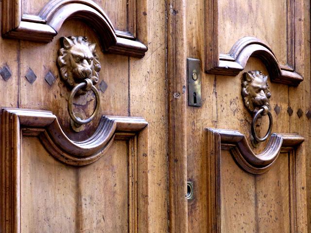 Löwe Türklopfer aus Messing an einer aufwendig gearbeiteten Holztür