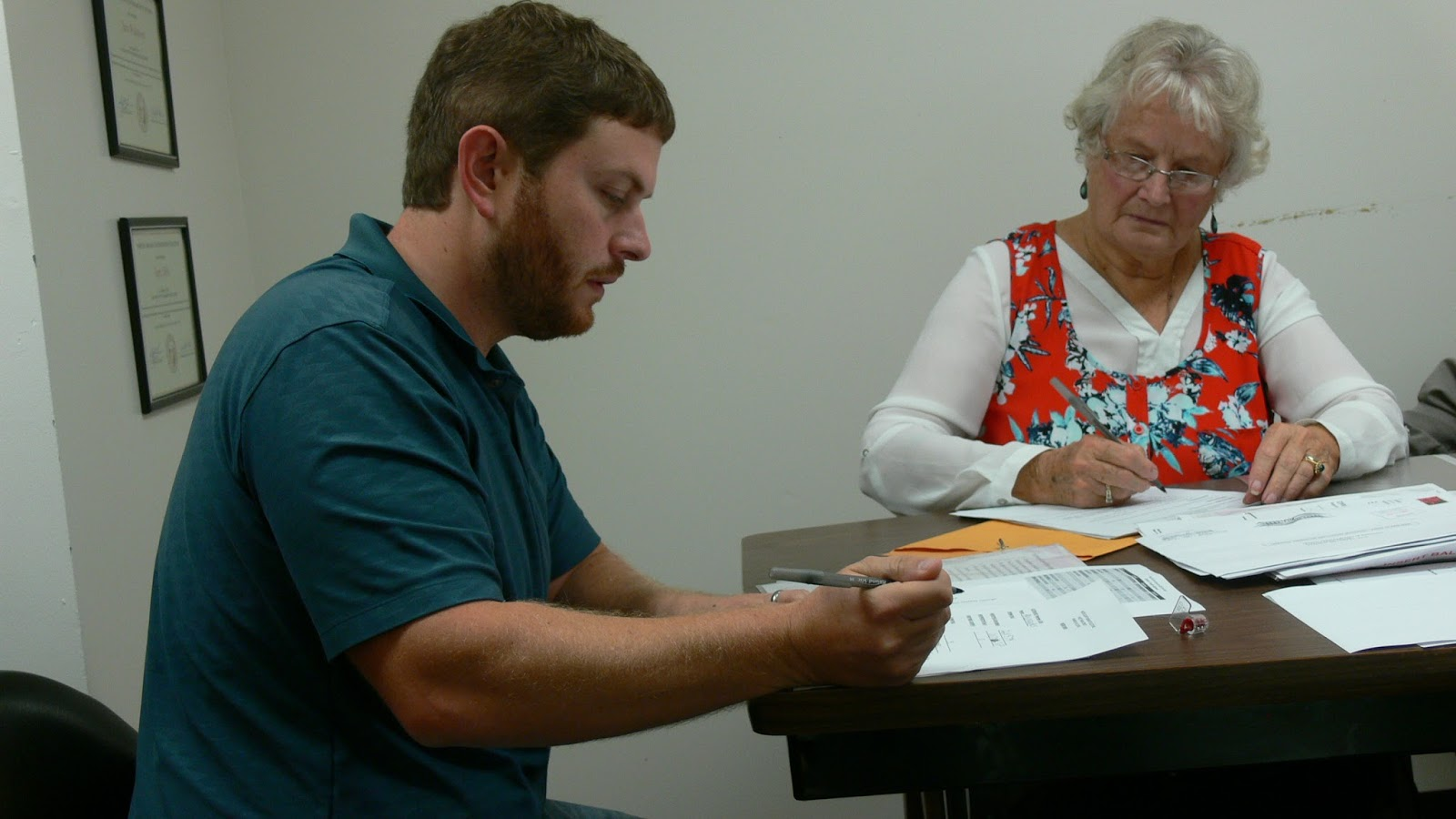 Board of Elections Chairman Luke Bateman signs a document attesting to the security of the voting machine seal used for counting the Provisional Ballots