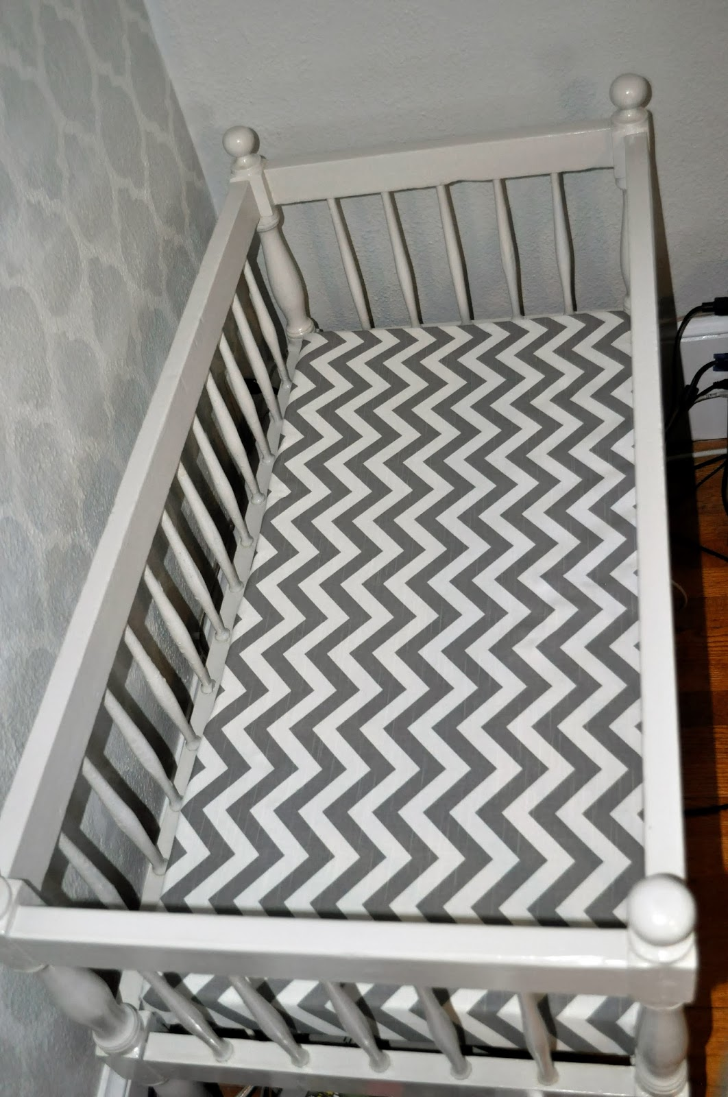 painted vintage grey wooden crib with chevron cushion