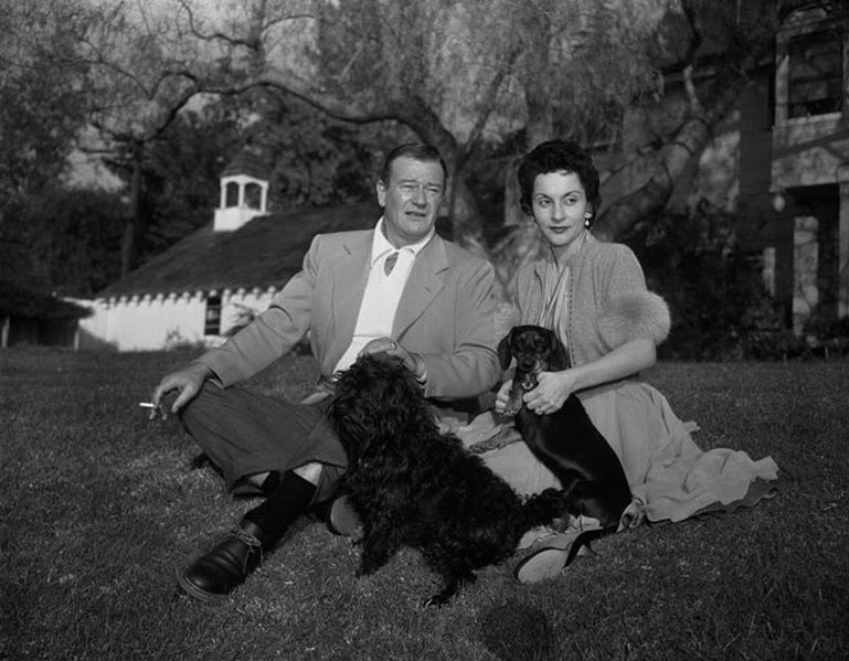 John Wayne and his wife Pilar Pallete posing with two furry family members.