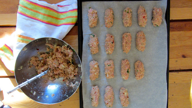 ground turkey mixture in a stainless bowl with a parchment lined cookie sheet with formed raw fingers ready for cooking