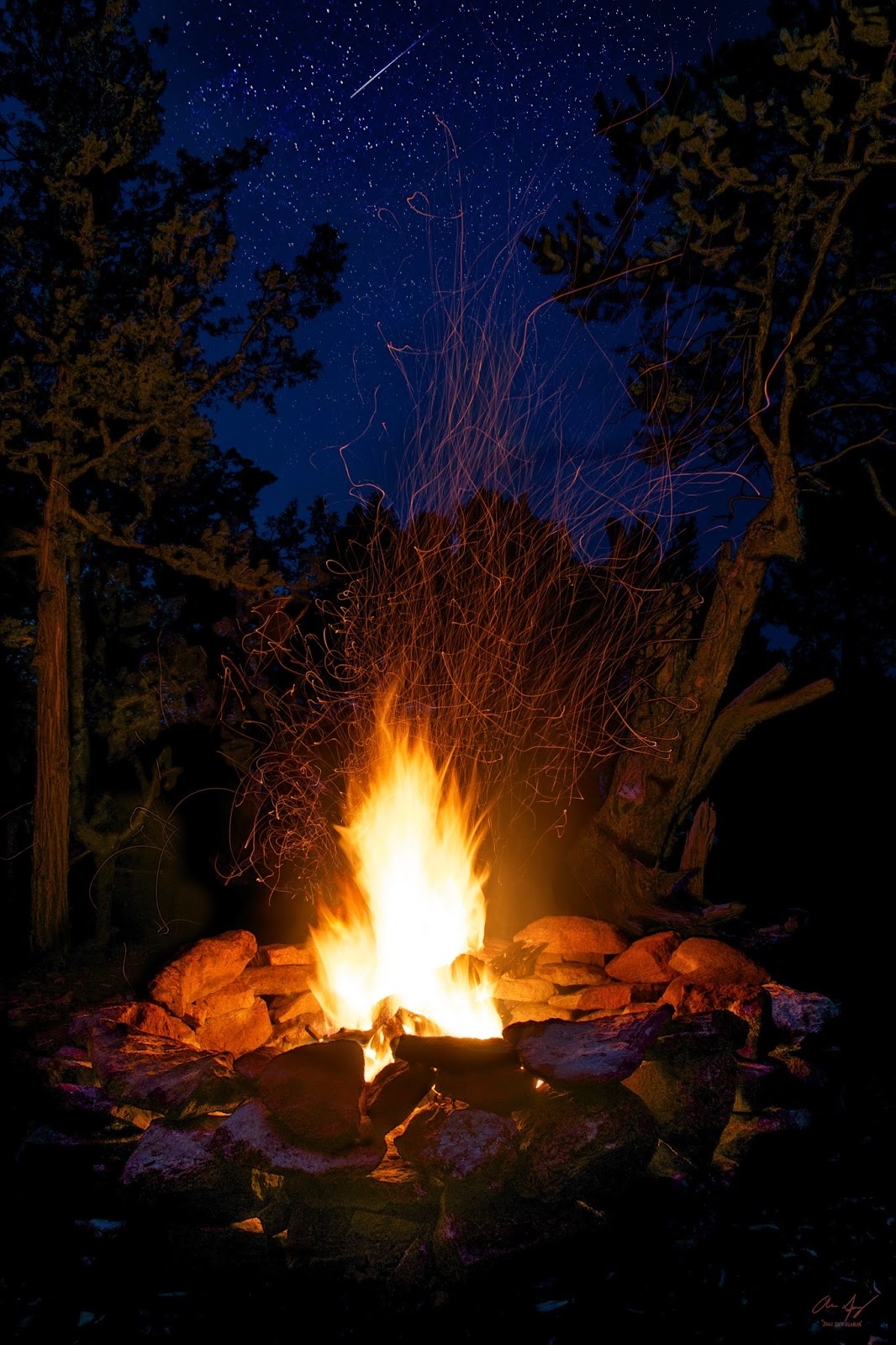 campfire with flames sparks and shooting star camping forest fire