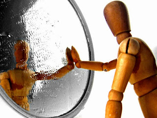 A wooden man leaning against a mirror reflecting himself