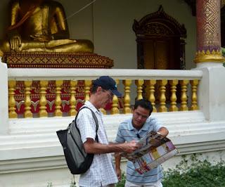 Um rapaz indica a um turista algo em um mapa, como se estivesse lhe dando uma informação de como chegar a aquele lugar.