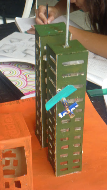 maqueta muestra las torres gemelas impactada por un avión de papel