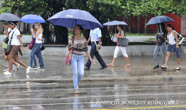 Transeúntes caminan por la calle 23 protegidos por sombrillas bajo las intensas lluvias que azotan La Habana, Cuba, el 5 de junio de 2013.