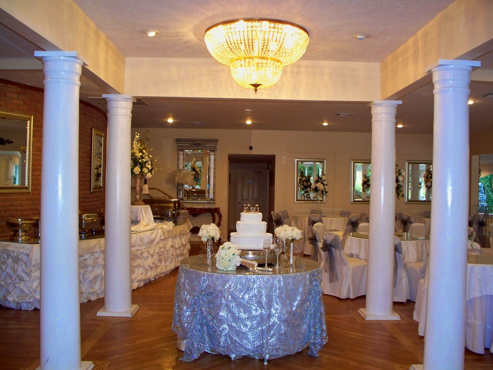 the ballroom has a bridal table guest tables a sound system area a dance floor area food tables a sign in table with a special castle guest book