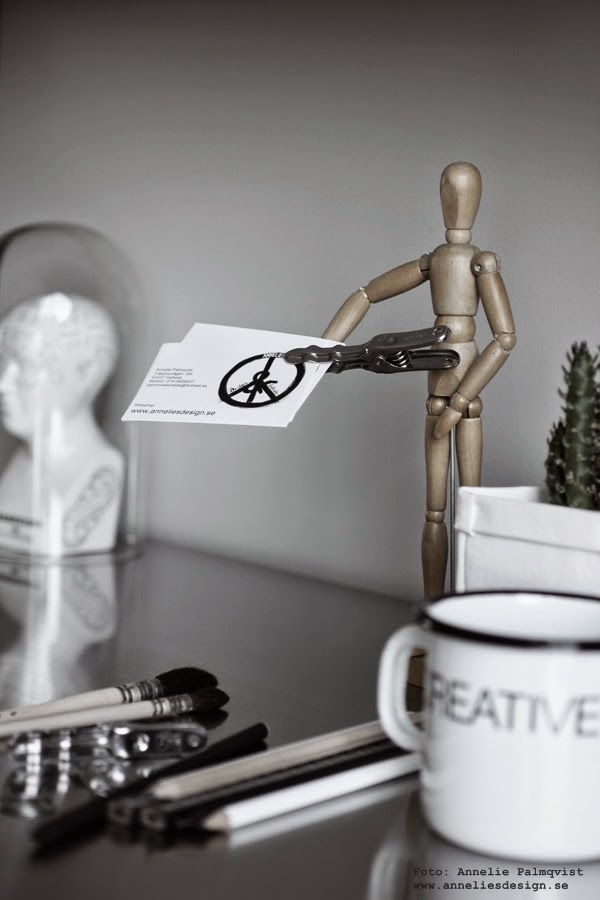 manekin, visitkort, svart och vitt, trären detalj, detaljer, arbetsrum, arbetsrummet, penel, penslar, rostfri bänkskiva, skrivbord, på skrivbordet, emaljkopp, plåtkopp, svart och vitt, klämma, grå vägg,
