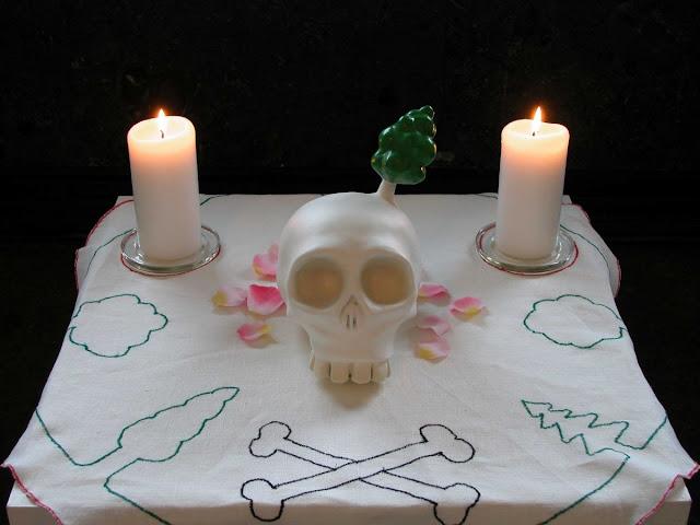 To lys på et bord - Kranium og stearinlys på bord med broderet dug -- The Skull by Fredrik Raddum