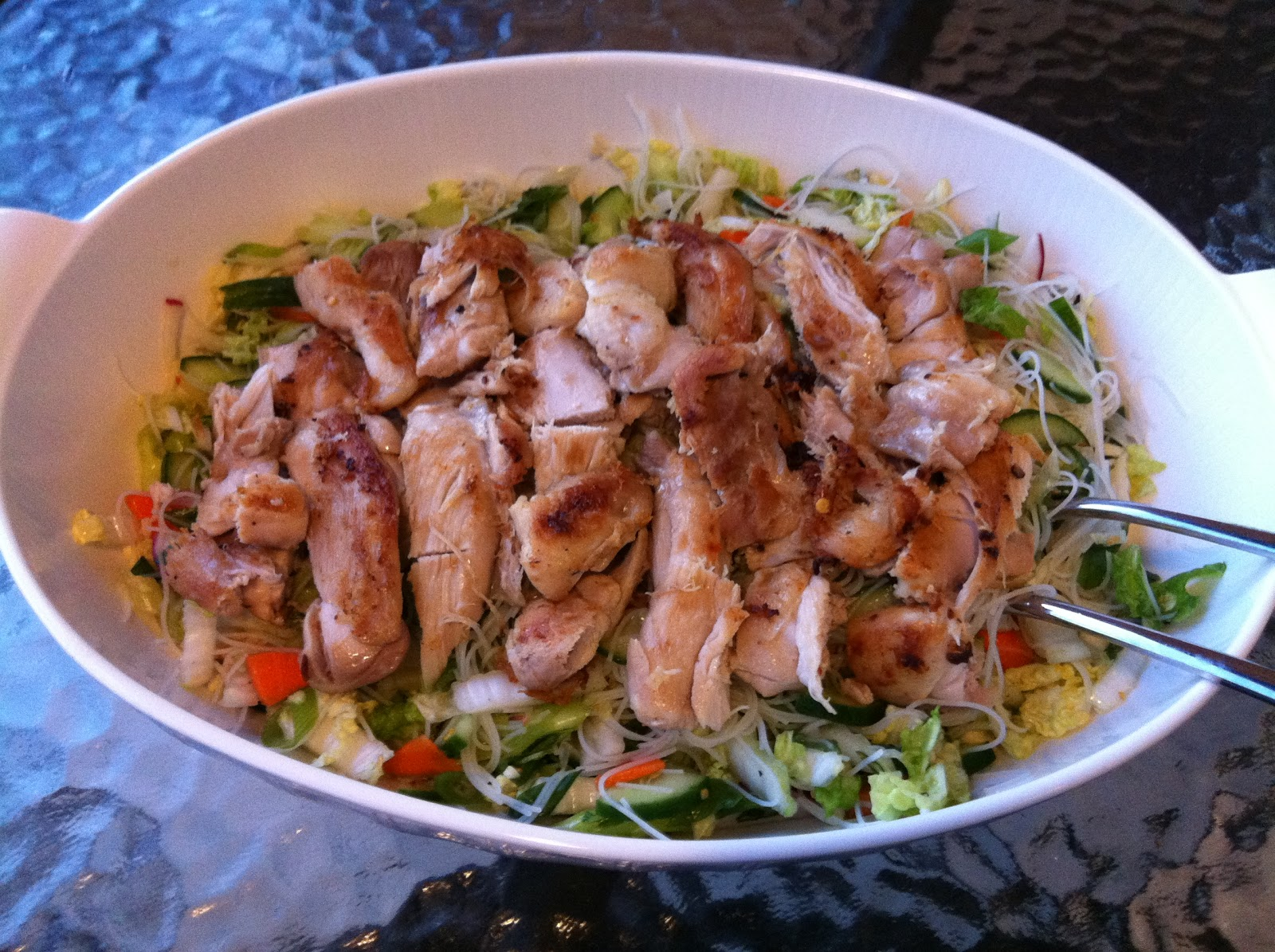 spicy marinated chicken thighs with noodle salad and fresh vegetables