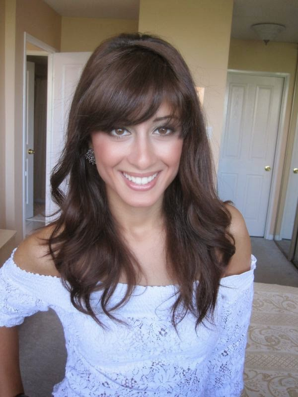 Hairstyle with front fringe and wavy curls falling down.