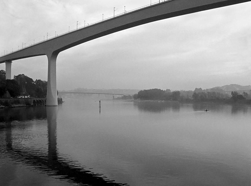 A ponte em primeiro plano com o seu reflexo na água numa manhã com bastante neblina